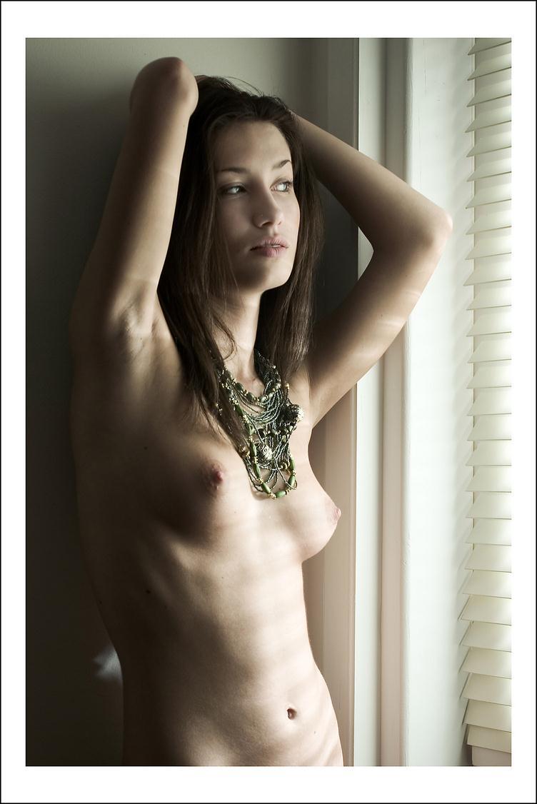 позирует у окна